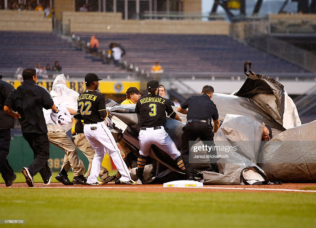 Andrew McCutchen and Sean Rodriguez of the Pittsburgh Pirates help out members of the grounds crew by holding down the tarp as heavy wind and rain...