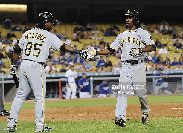Andrew McCutchen celebrates with teammate Lastings Milledge of the Pittsburgh Pirates after scoring in the 13th inning against the Los Angeles...