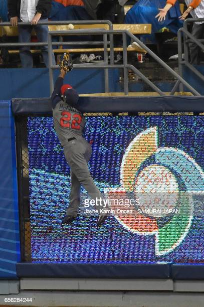 Andrew McCutchen of team United States reaches to catch a homerun hit by Ryosuke Kikuchi of team Japan in the sixth inning during Game 2 of the...