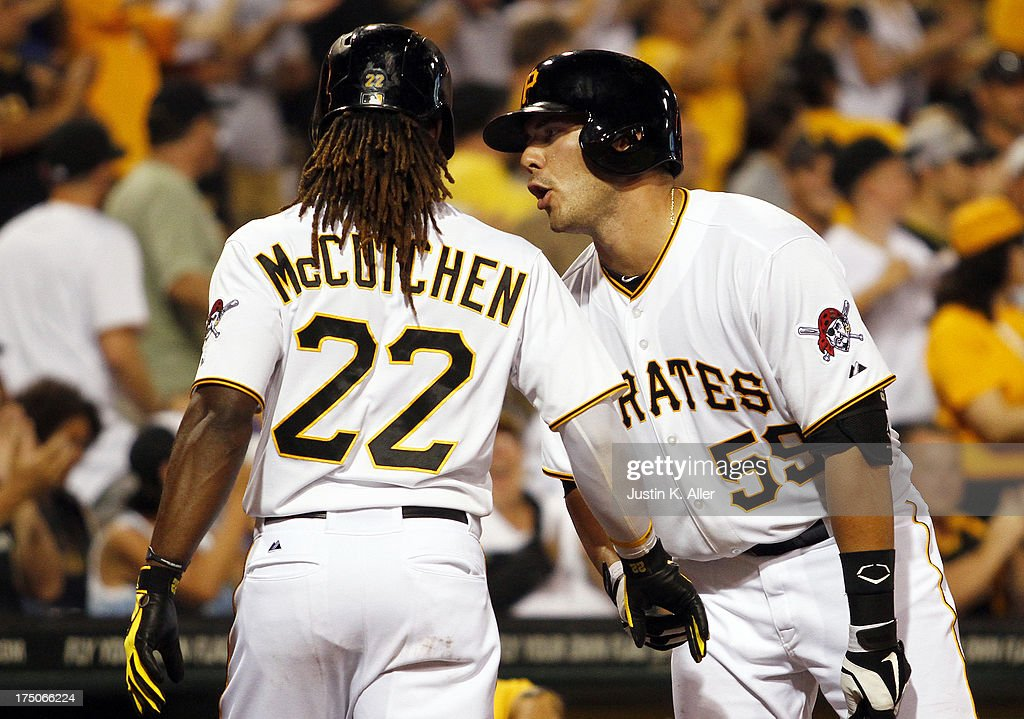 <a gi-track='captionPersonalityLinkClicked' href=/galleries/search?phrase=Andrew+McCutchen&family=editorial&specificpeople=2364814 ng-click='$event.stopPropagation()'>Andrew McCutchen</a> #22 of the Pittsburgh Pirates celebrates with Russell Martin #55 after scoring on a seventh inning RBI double against the St. Louis Cardinals during game two of a doubleheader on July 30, 2013 at PNC Park in Pittsburgh, Pennsylvania.