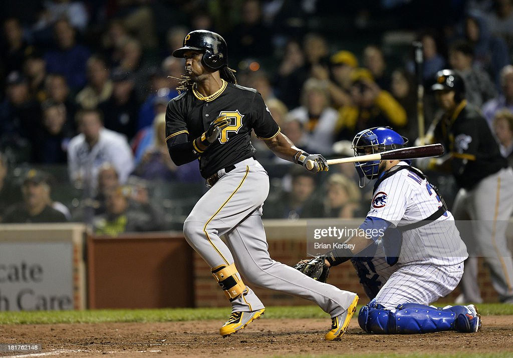 <a gi-track='captionPersonalityLinkClicked' href=/galleries/search?phrase=Andrew+McCutchen&family=editorial&specificpeople=2364814 ng-click='$event.stopPropagation()'>Andrew McCutchen</a> #22 of the Pittsburgh Pirates follows through on an RBI single scoring teammate Starling Marte #6 as <a gi-track='captionPersonalityLinkClicked' href=/galleries/search?phrase=Dioner+Navarro&family=editorial&specificpeople=593062 ng-click='$event.stopPropagation()'>Dioner Navarro</a> #30 of the Chicago Cubs catches during the eighth inning at Wrigley Field on September 24, 2013 in Chicago, Illinois.