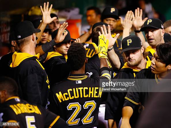 Andrew McCutchen of the Pittsburgh Pirates is congratulated by teammates in the dugout after scoring in the fourth inning against the Milwaukee...