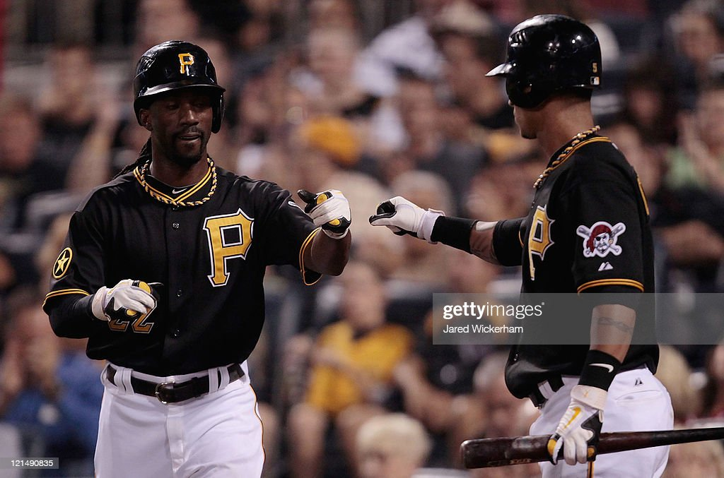 Andrew McCutchen of the Pittsburgh Pirates is congratulated by teammate Ronny Cedeno after scoring against the Cincinnati Reds during the game on...