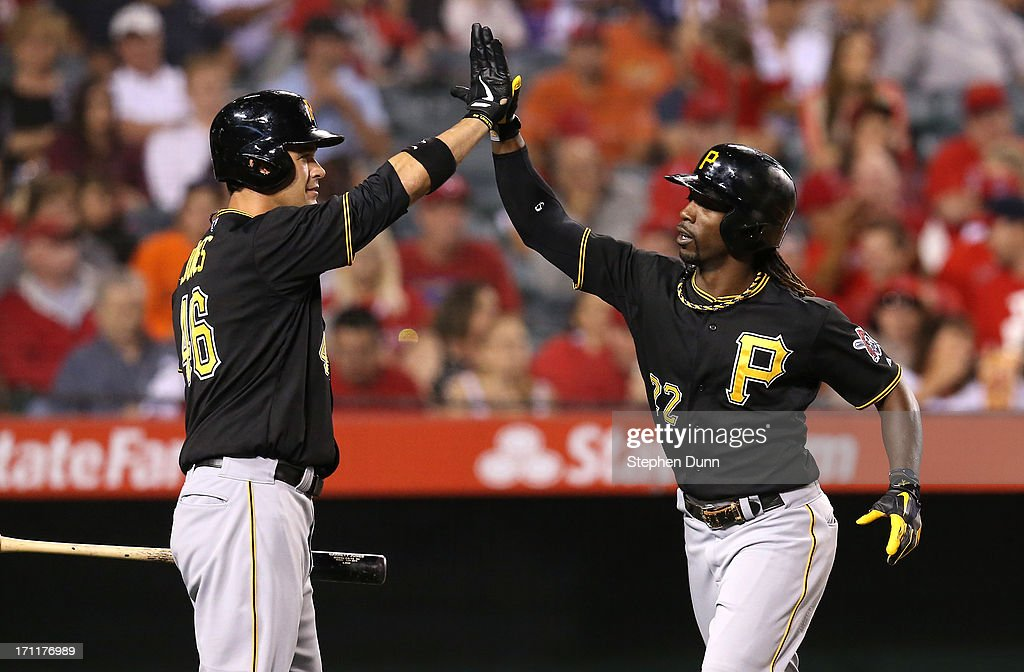Andrew McCutchen #22 of the Pittsburgh Pirates is greeted by Garrett Jones #46 as he returns to the dugout after hitting a solo home run in the fifth inning against the Los Angeles Angels of Anaheim at Angel Stadium of Anaheim on June 22, 2013 in Anaheim, California.