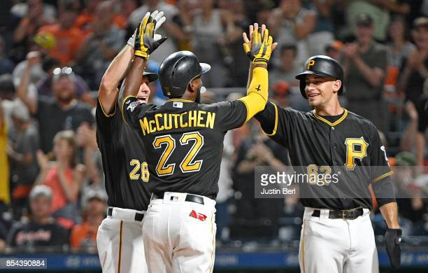 Andrew McCutchen of the Pittsburgh Pirates is greeted by Max Moroff and Adam Frazier as he crosses home plate after hitting a grand slam home run in...