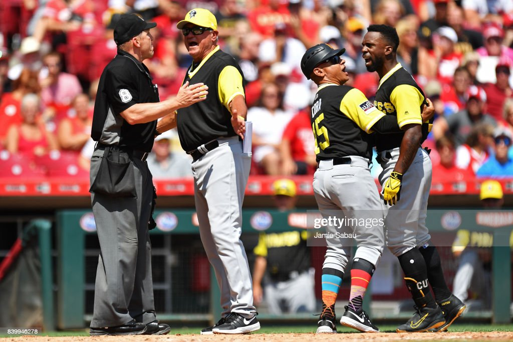 Andrew McCutchen #22 of the Pittsburgh Pirates is held back by third base coach Joey Cora #15 of the Pittsburgh Pirates as he and Manager Clint Hurdle #13 of the Pittsburgh Pirates argue with umpire Jeff Kellogg in the fourth inning after Kellogg failed to call a time out against the Cincinnati Reds at Great American Ball Park on August 27, 2017 in Cincinnati, Ohio. Pittsburgh defeated Cincinnati 5-2.