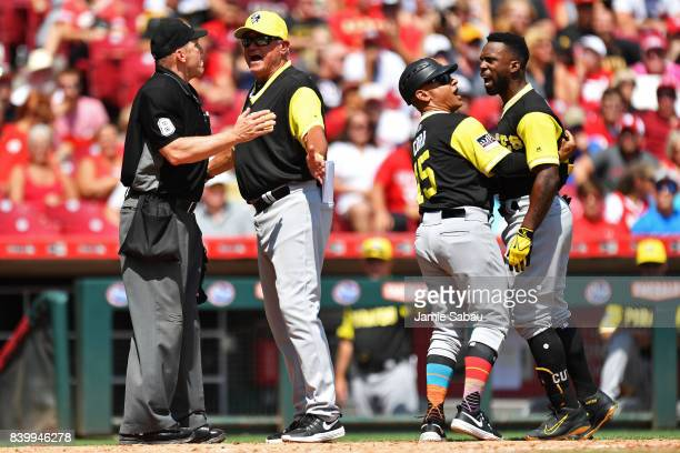 Andrew McCutchen of the Pittsburgh Pirates is held back by third base coach Joey Cora of the Pittsburgh Pirates as he and Manager Clint Hurdle of the...