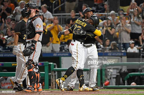 Andrew McCutchen of the Pittsburgh Pirates is hugged by Starling Marte as he crosses home plate after hitting a grand slam home run in the second...