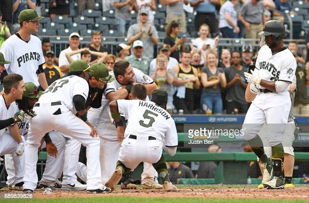 Andrew McCutchen of the Pittsburgh Pirates is met by teammates at home plate after hitting a walk off home run in the ninth inning to give the...