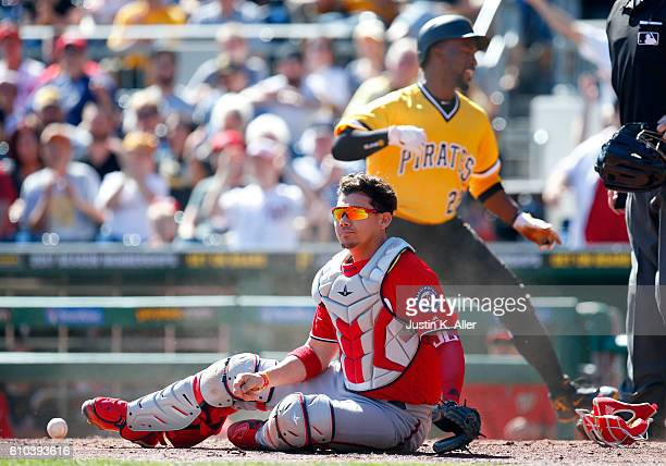 Andrew McCutchen of the Pittsburgh Pirates scores past Jose Lobaton of the Washington Nationals in the first inning on a foul out to the catcher...