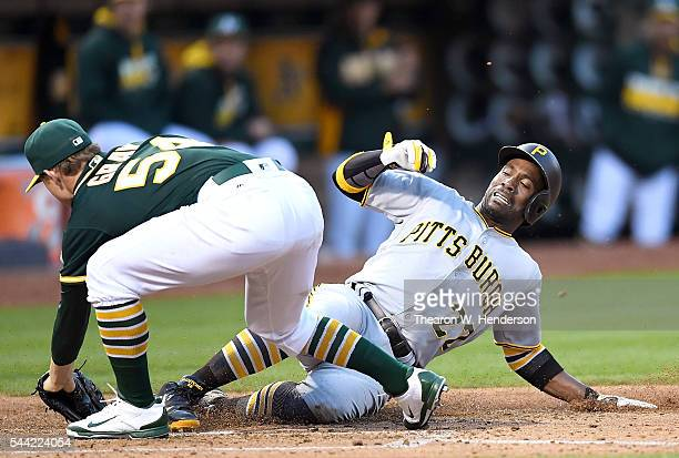 Andrew McCutchen of the Pittsburgh Pirates scores sliding under Sonny Gray of the Oakland Athletics in the top of the fourth inning at Oco Coliseum...