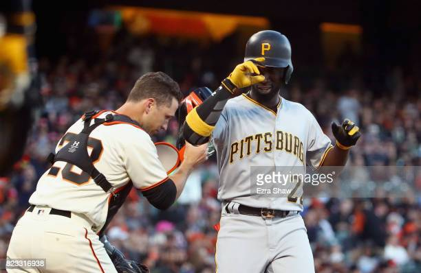 Andrew McCutchen of the Pittsburgh Pirates tips his hat after he a threerun home run while Buster Posey of the San Francisco Giants runs out to talk...