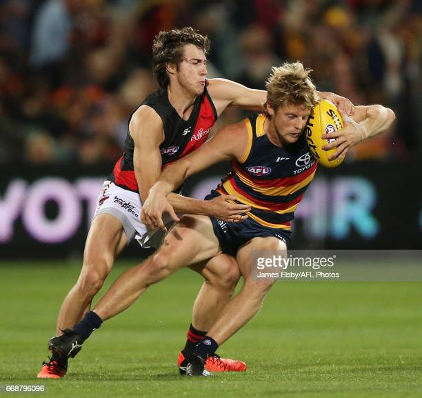 Andrew McGrath of the Bombers tackles Rory Sloane of the Crows during the 2017 AFL round 04 match between the Adelaide Crows and the Essendon Bombers...
