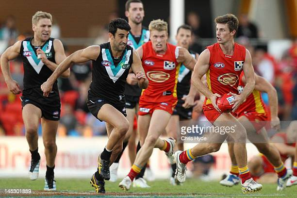 Andrew McQualter of the Suns runs from Domenic Cassisi of the Power during the round nine AFL match between the Gold Coast Suns and Port Adelaide...