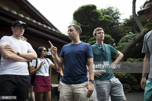 Andrew Mitola center left speaks to an attendee as they walk toward a Japanese garden during a cultural experience program part of Mitsubishi UFJ...