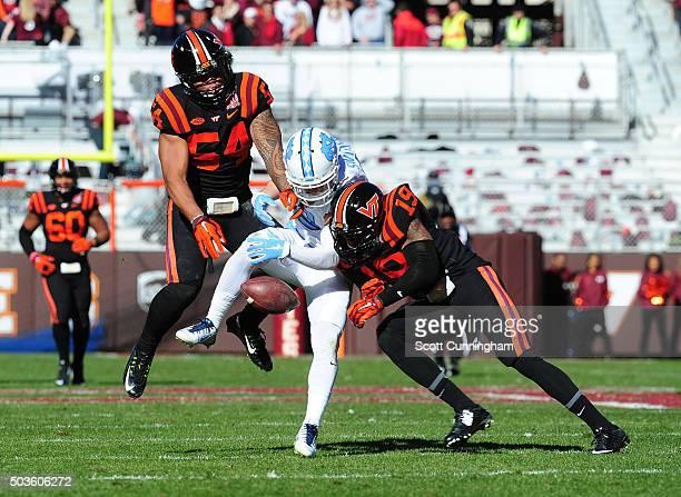 Andrew Motuapuaka and Chuck Clark of the Virginia Tech Hokies break up a pass intended for Ryan Switzer of the North Carolina Tar Heels on November...