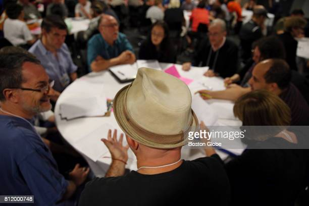 Andrew 'Murdoch' Chaikin center discusses a puzzle with his table during the National Puzzlers League convention at the Revere Hotel in Boston MA on...