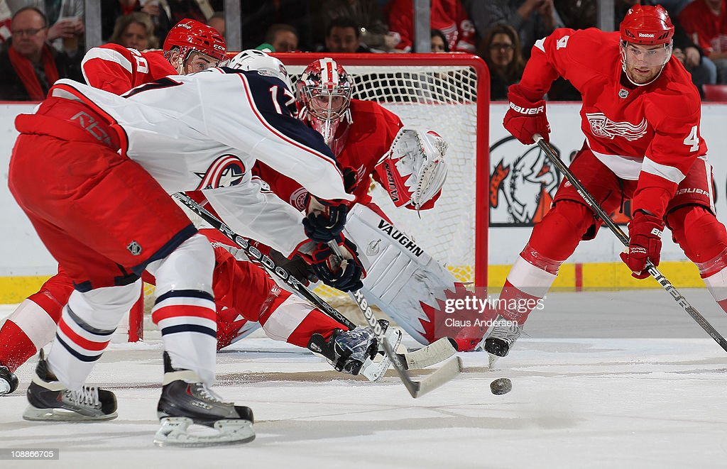 Andrew Murray #17 of the Columbus Blue Jackets tries to slip a puck past Jimmy Howard #35 and Jakub Kindl #4 of the Detroit Red Wings in a game on February 4, 2011 at the Joe Louis Arena in Detroit, Michigan. The Blue Jackets defeated the Red Wings 3-0.