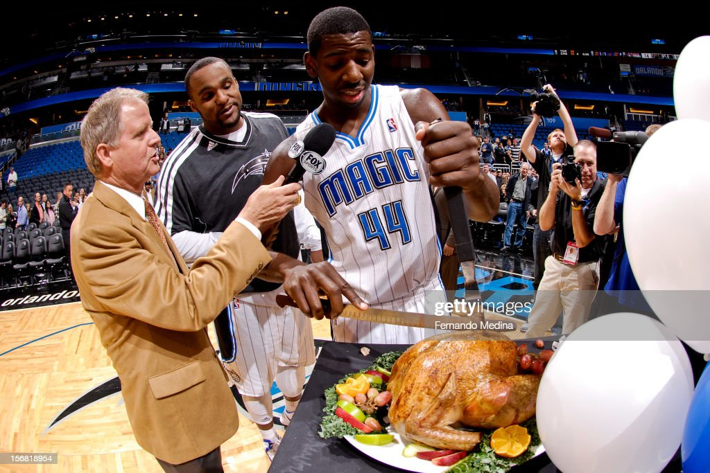 Andrew Nicholson #44 and Glen Davis #11 of the Orlando Magic cut a Thanksgiving turkey following their team's game against the Detroit Pistons on November 21, 2012 at Amway Center in Orlando, Florida.