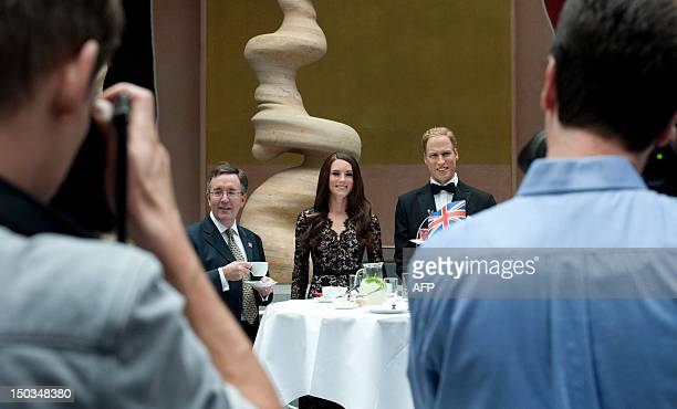 Andrew Noble British viceambassador to Germany poses for photographers and a camera team next to wax likenesses of Britain's Prince William and his...