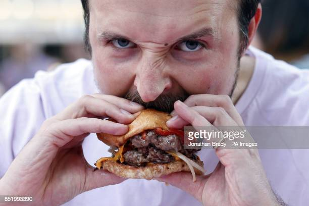Andrew Phillimore from Finsbury eats a triple decker hamburger during an event to launch the UK's first 'National Burger Day' held at Dalston Yard...