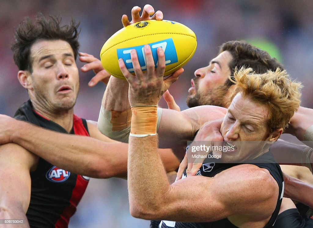 Andrew Phillips of the Blues marks the ball against Matt Dea of the Bombers during the round six AFL match between the Carlton Blues and the Essendon Bombers at Melbourne Cricket Ground on May 1, 2016 in Melbourne, Australia.