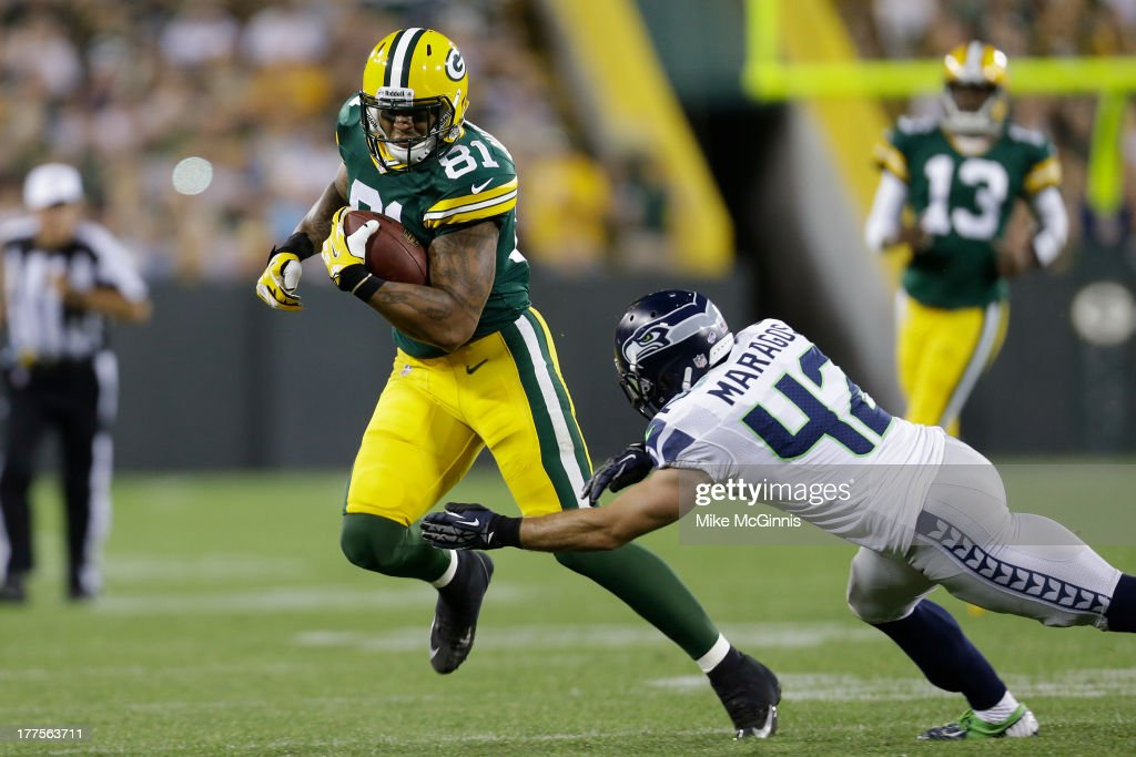 Andrew Quarless #81 of the Green Bay Packers runs for yards before getting tackled by Chris Maragos #42 of the Seattle Seahawks during the game at Lambeau Field on August 23, 2013 in Green Bay, Wisconsin.