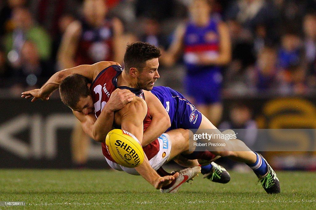 Andrew Raines of the Lions is tackled during the round 13 AFL match between the Western Bulldogs and the Brisbane Lions at Etihad Stadium on June 23, 2012 in Melbourne, Australia.