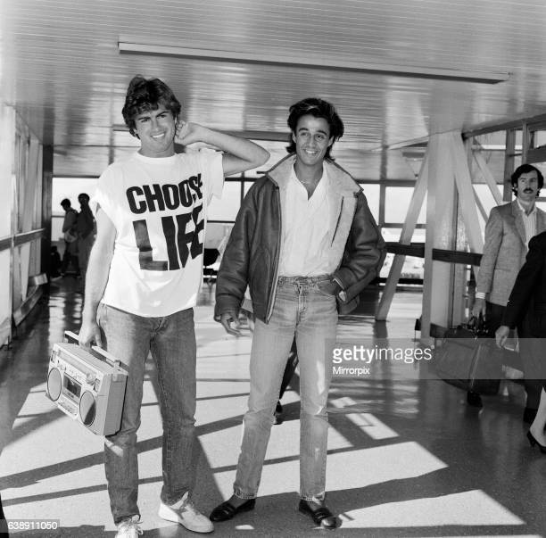 Andrew Ridgeley and George Michael of the pop group Wham arriving at London airport George Michael is wearing a 'Choose Life' tshirt and holding a...