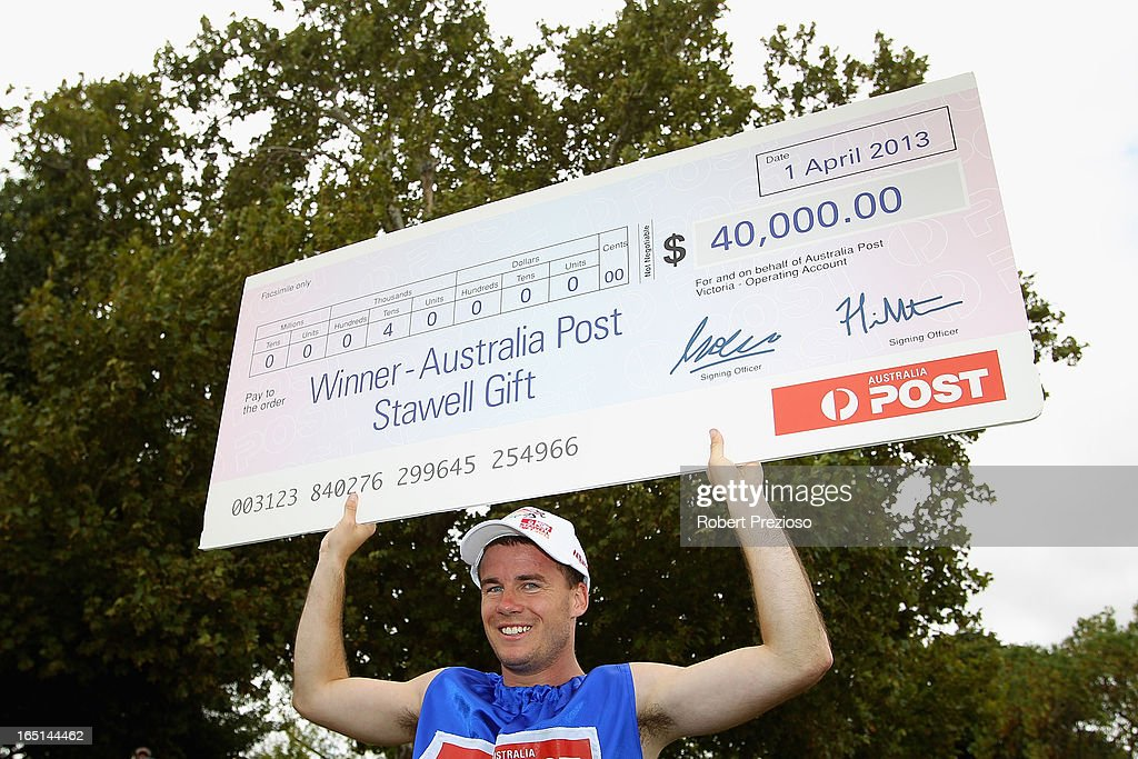 Andrew Robinson of Tasmania holds the winners cheque after winning the Australia Post Stawell Gift 120m Final during the 2013 Stawell Gift carnival at Central Park on April 1, 2013 in Stawell, Australia.