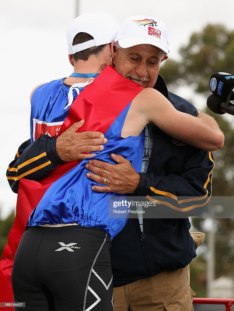 Andrew Robinson of Tasmania hugs his coach Ray Quarrell after winning the Australia Post Stawell Gift 120m Final during the 2013 Stawell Gift carnival at Central Park on April 1, 2013 in Stawell, Australia.