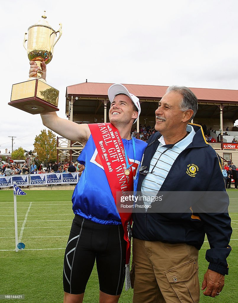 Andrew Robinson of Tasmania poses for photos with coach Ray Quarrell after winning the Australia Post Stawell Gift 120m Final during the 2013 Stawell Gift carnival at Central Park on April 1, 2013 in Stawell, Australia.