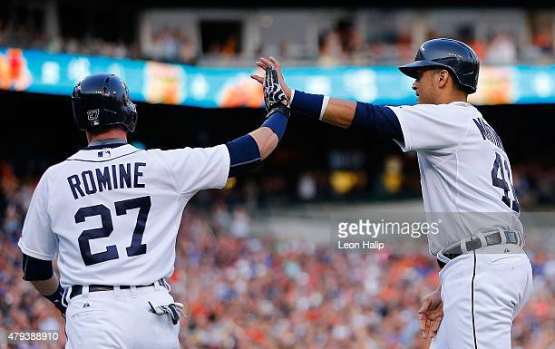 Andrew Romine of the Detroit Tigers and Victor Martinez celebrate after scoring during the fourth inning of the game against the Toronto Blue Jays on...