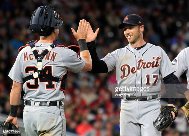 Andrew Romine of the Detroit Tigers is congratulated by teammate James McCann after pitching to the Minnesota Twins in the eighth inning during of...