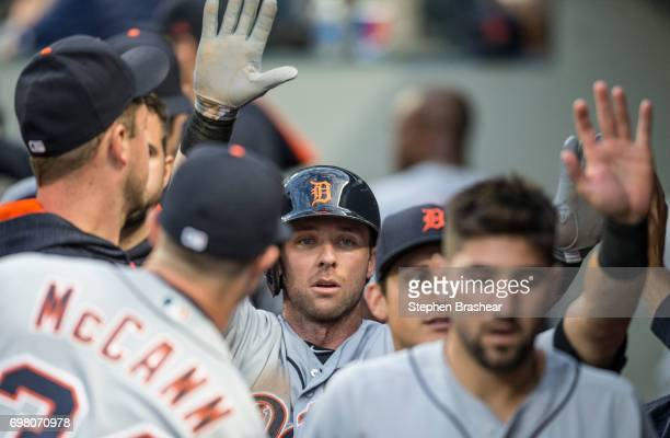 Andrew Romine of the Detroit Tigers is congratulated by teammates in teh dugout after scoring on on RBI ground out by Alex Avila of the Detroit...