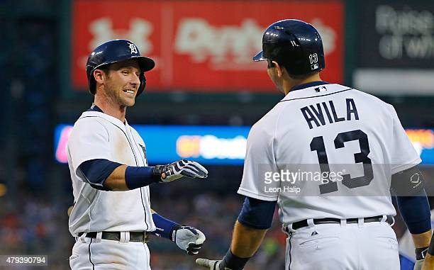 Andrew Romine of the Detroit Tigers scores on the JD Martinez single and celebrates with Alex Avila during the seventh inning of the game against the...