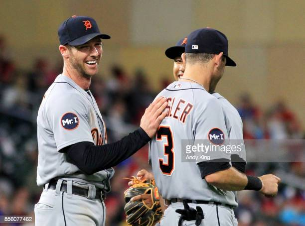 Andrew Romine of the Detroit Tigers shares a laugh teammates Ian Kinsler and Jose Iglesias after Romine pitched in the eighth inning during of their...