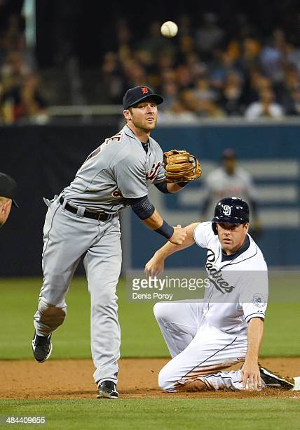 Andrew Romine of the Detroit Tigers turns a double play as Seth Smith of the San Diego Padres slides during the third inning of an interleague...