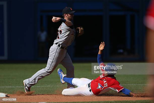 Andrew Romine of the Detroit Tigers turns a double play in the tenth inning during MLB game action as Marcus Stroman of the Toronto Blue Jays slides...