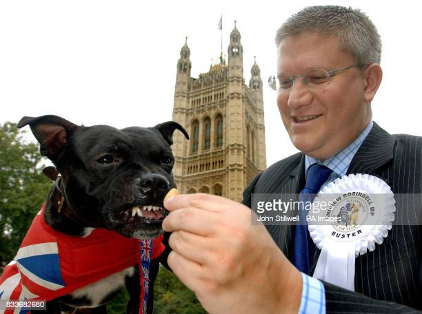 Andrew Rosindell MP for Romford Essex feeds his dog Buster a 3 yearold Staffordshire Bull Terrier before the Westminster MP's dog of the year contest...