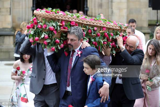 The father of Saffie Roussos holds his son Xander Roussos whilst carrying the coffin of his daughter following the funeral of the young Manchester...