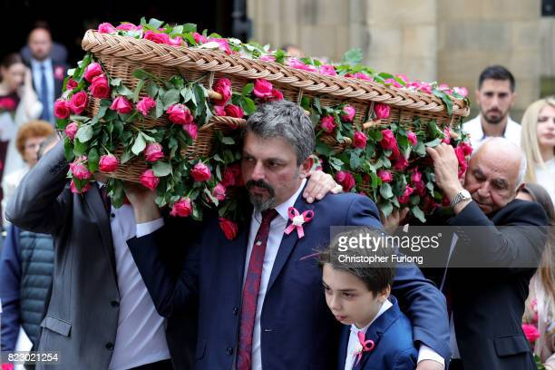Andrew Roussos the father of Saffie Roussos holds his son Xander Roussos whilst carrying the coffin of his daughter following the funeral of the...