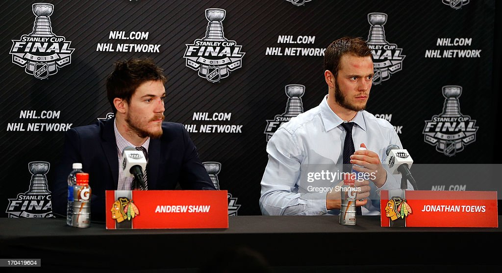 Andrew Shaw #65 and Jonathan Toews #19 of the Chicago Blackhawks answers questions from the media at a post game press conference after he scored the game-winning goal in the third overtime to give them a 4-3 win against the Boston Bruins in Game One of the 2013 NHL Stanley Cup Final at United Center on June 12, 2013 in Chicago, Illinois.