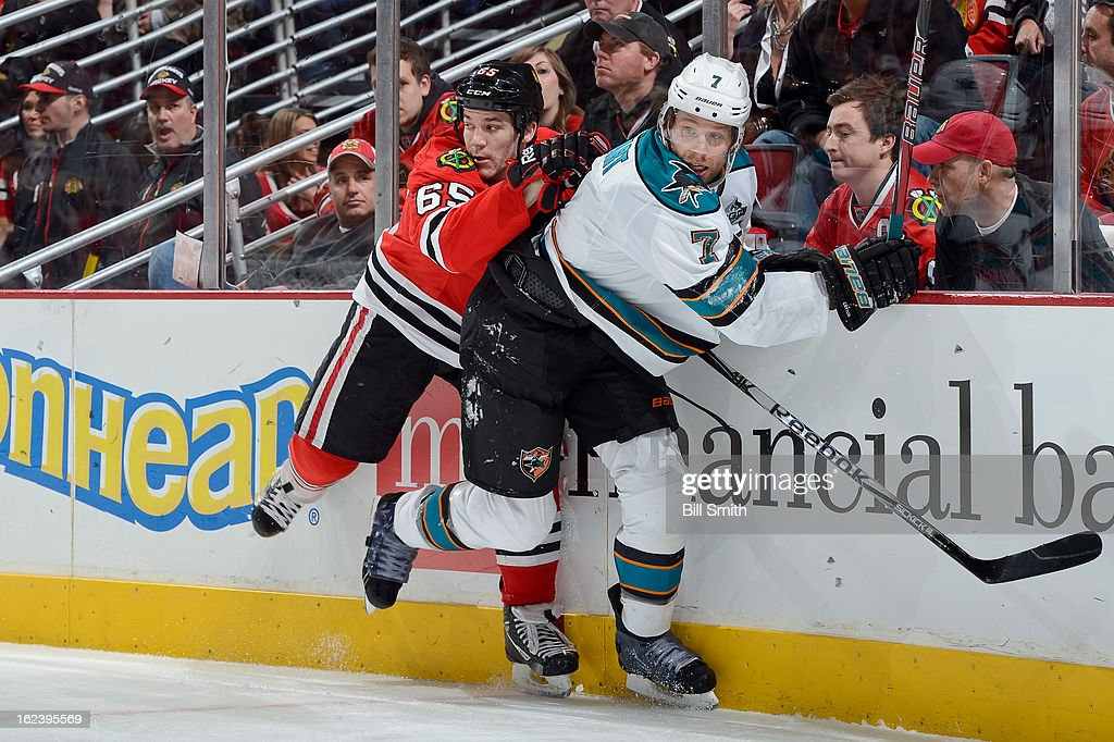 Andrew Shaw #65 of the Chicago Blackhawks and <a gi-track='captionPersonalityLinkClicked' href=/galleries/search?phrase=Brad+Stuart+-+Ice+Hockey+Player&family=editorial&specificpeople=213995 ng-click='$event.stopPropagation()'>Brad Stuart</a> #7 of the San Jose Sharks skate around the boards during the NHL game on February 22, 2013 at the United Center in Chicago, Illinois.
