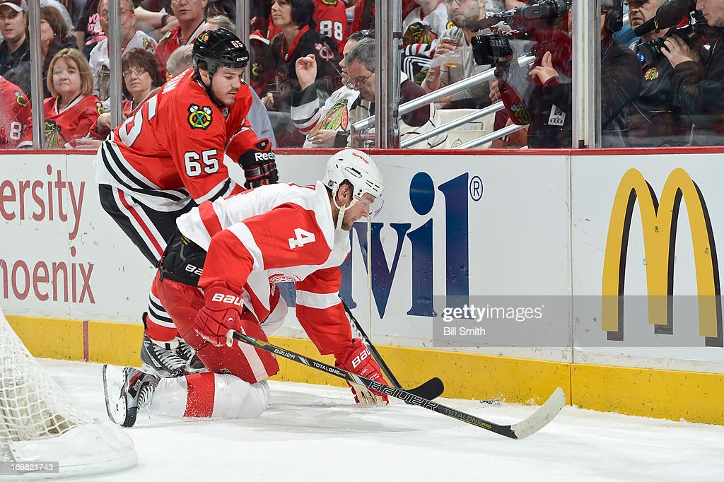 Andrew Shaw #65 of the Chicago Blackhawks and Jakub Kindl #4 of the Detroit Red Wings fight for the puck along the boards in Game One of the Western Conference Semifinals during the 2013 Stanley Cup Playoffs at the United Center on May 15, 2013 in Chicago, Illinois.