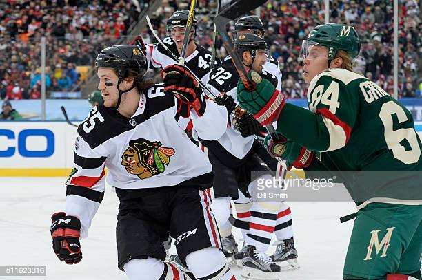 Andrew Shaw of the Chicago Blackhawks and Mikael Granlund of the Minnesota Wild watch for the puck in the second period of the 2016 Coors Light...