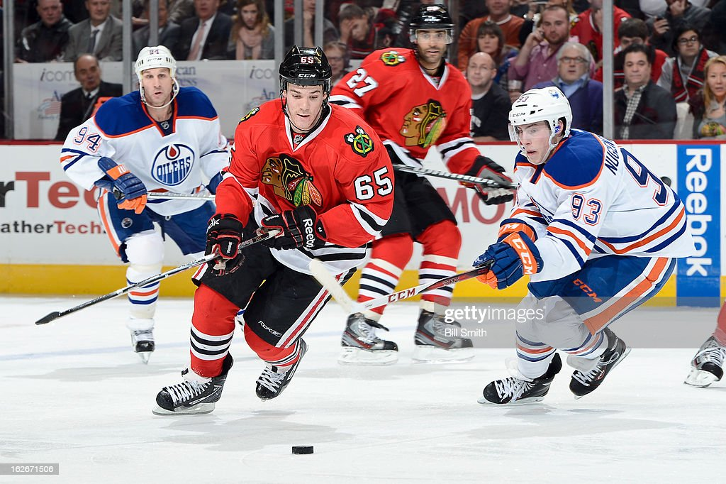 Andrew Shaw #65 of the Chicago Blackhawks and <a gi-track='captionPersonalityLinkClicked' href=/galleries/search?phrase=Ryan+Nugent-Hopkins&family=editorial&specificpeople=7144190 ng-click='$event.stopPropagation()'>Ryan Nugent-Hopkins</a> #93 of the Edmonton Oilers skate towards the puck during the NHL game on February 25, 2013 at the United Center in Chicago, Illinois.
