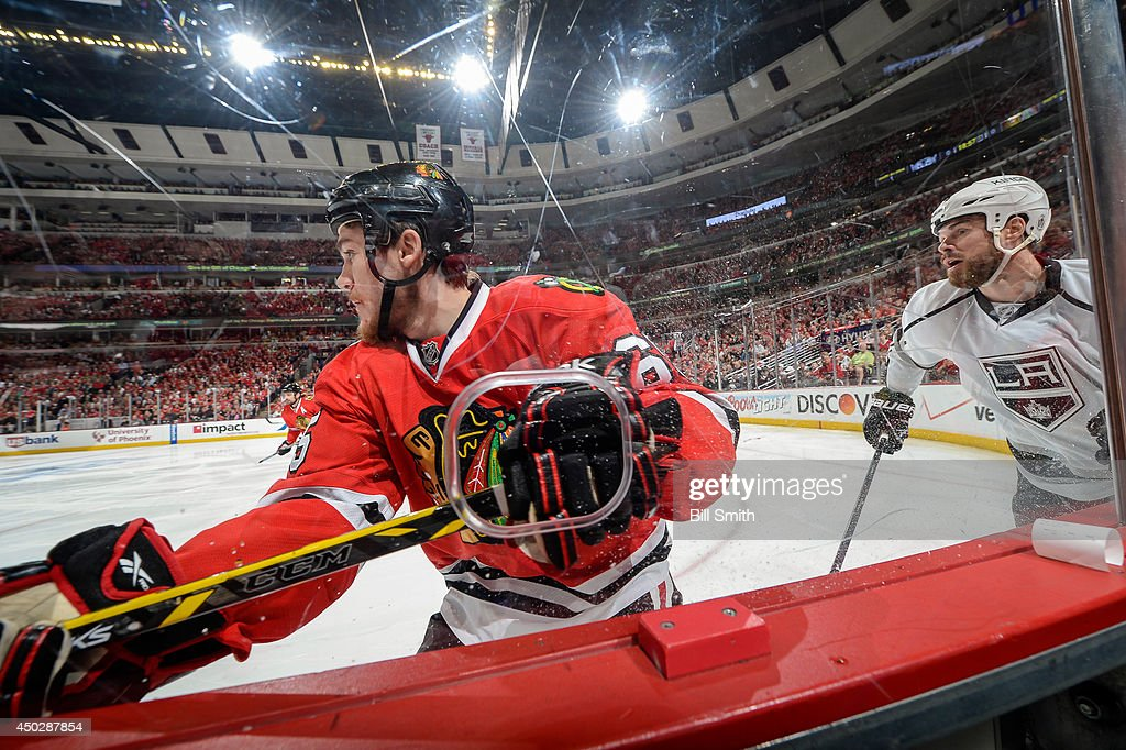 Andrew Shaw #65 of the Chicago Blackhawks and Willie Mitchell #33 of the Los Angeles Kings skate around the boards in Game Seven of the Western Conference Final during the 2014 NHL Stanley Cup Playoffs at the United Center on June 01, 2014 in Chicago, Illinois.
