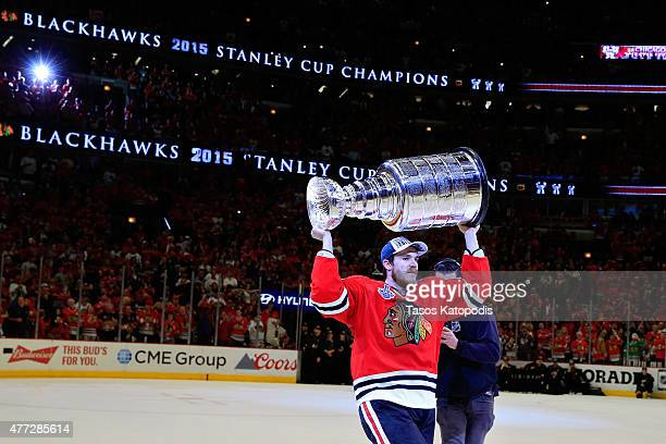 Andrew Shaw of the Chicago Blackhawks celebrates by kissing the Stanley Cup after defeating the Tampa Bay Lightning by a score of 20 in Game Six to...