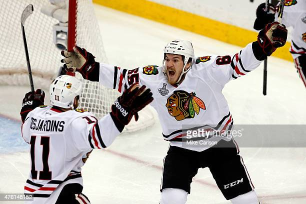 Andrew Shaw of the Chicago Blackhawks celebrates with teammate Andrew Desjardins after scoring a goal against Ben Bishop of the Tampa Bay Lightning...